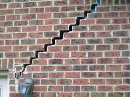 Why do brick walls crack in houses?