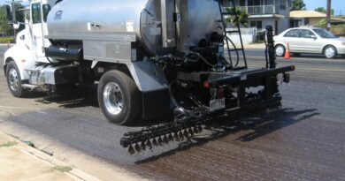 Why do construction workers spray water on the road while doing road work?